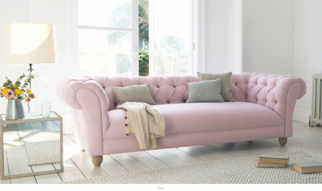 pink tufted sofa on white plant wood floor with rug and window behind it