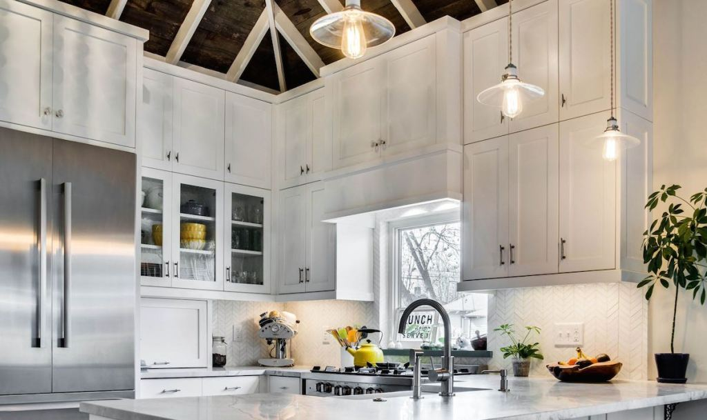 white kitchen cabinets with high ceilings white beans and wood plants on surface