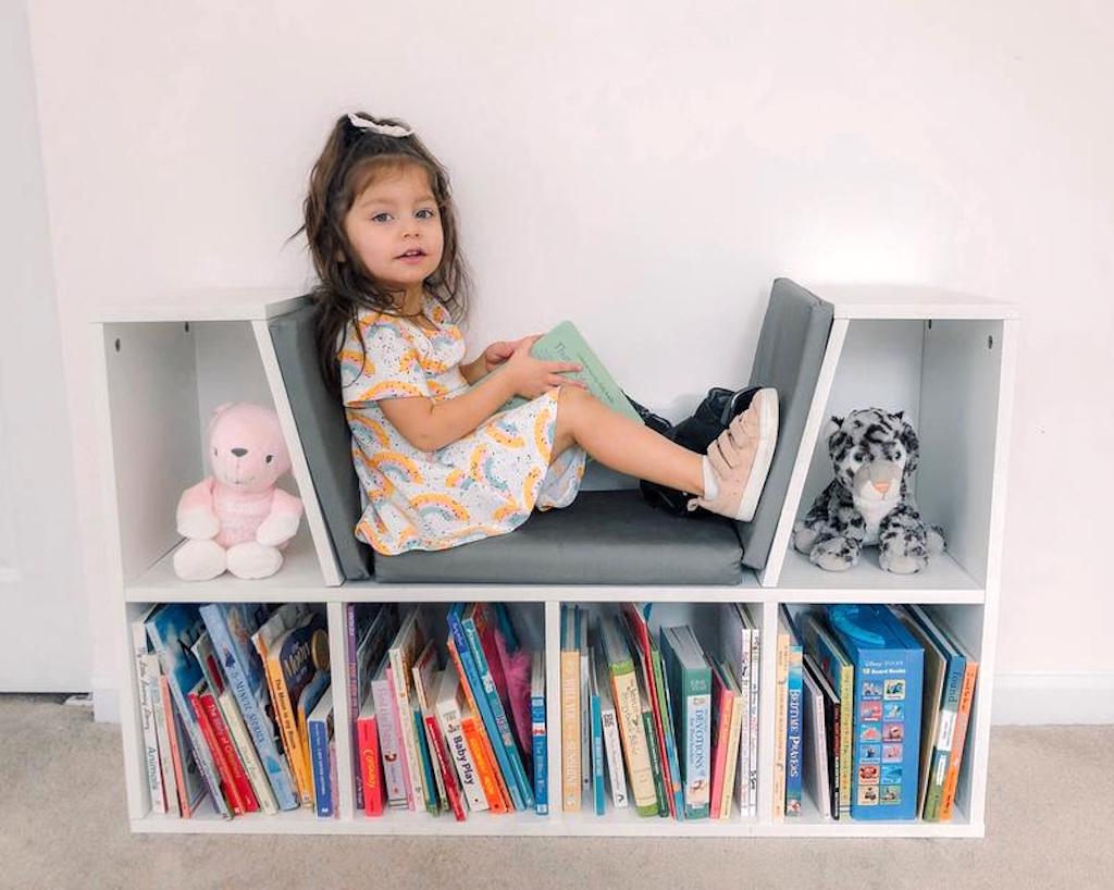 little girl sitting in 6-Cubbie Kids Bookcase w/ Reading Nook