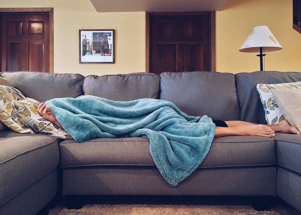 woman napping on the couch with a blanket