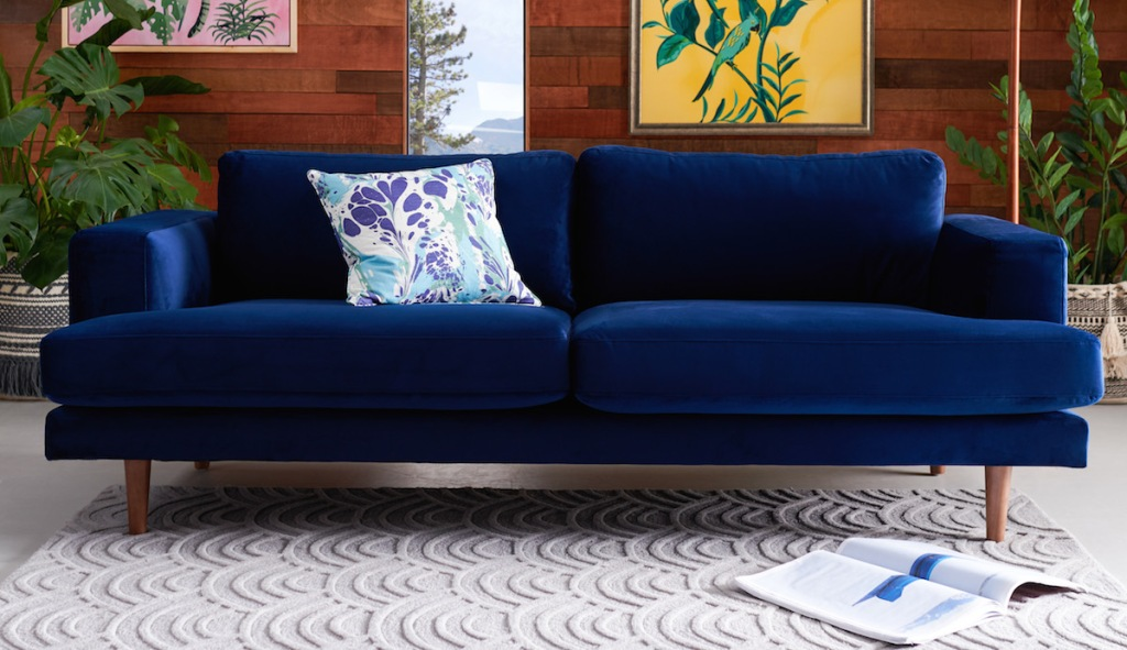 navy velvet couch in room with ivory textile rug and various bold decor pillows