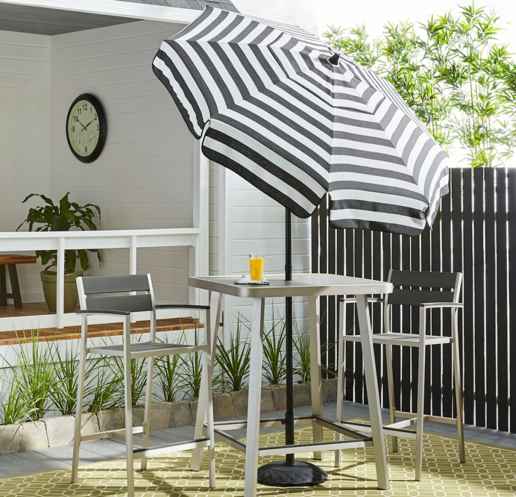 black and white stripe umbrella with bar table and two stainless steel chairs with fence and room in background
