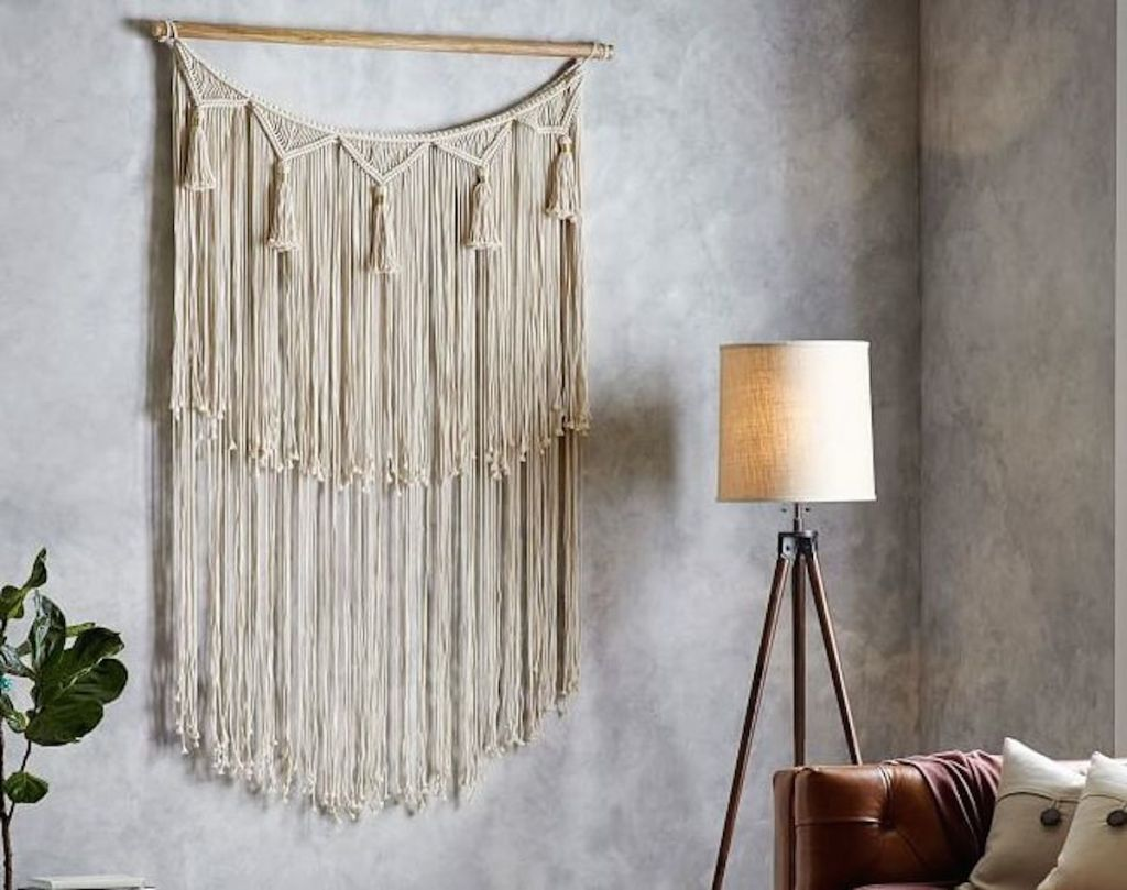 long macrame wall hanging on gray wall with lamp and leather couch in corner
