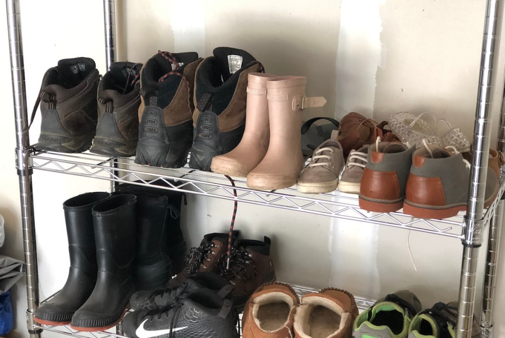 various styles of boots and shoes on metal shoe rack