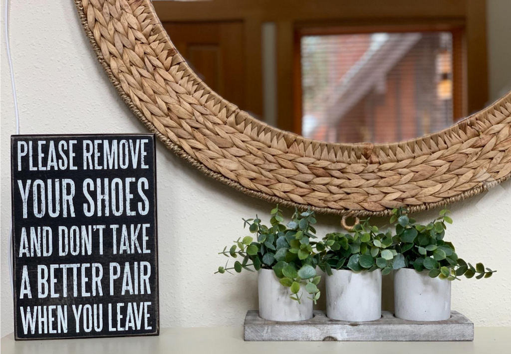 remove your shoes sign sitting on table with plants and mirror