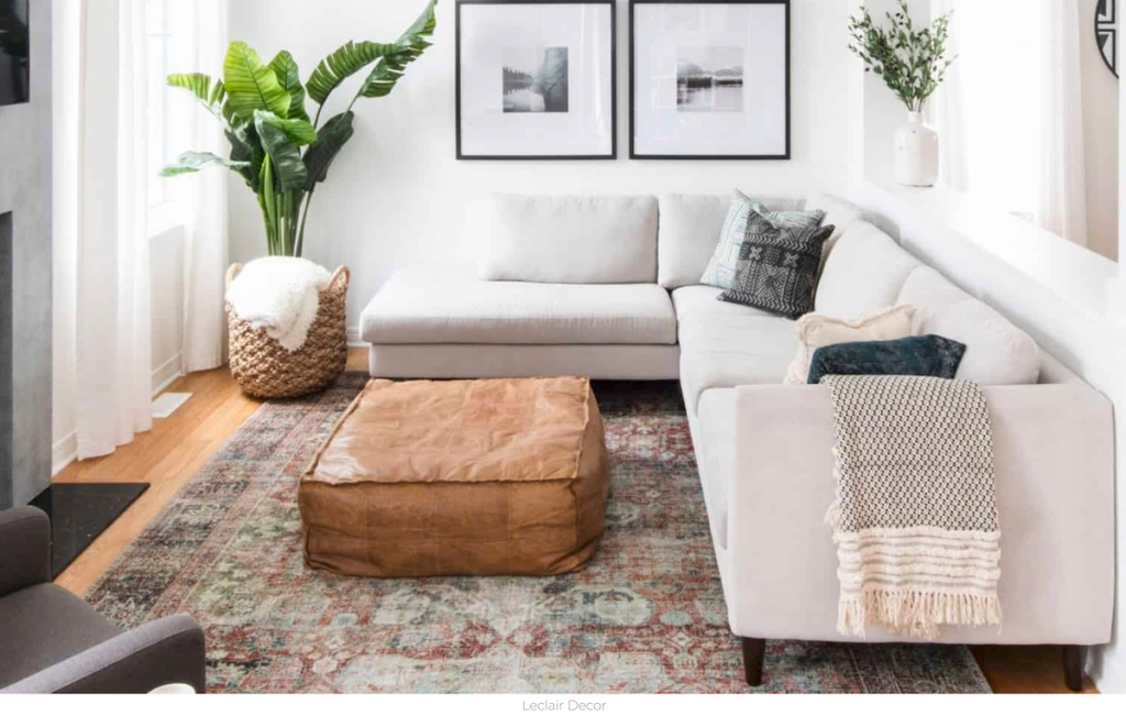 L-shaped gray sectional couch with pillows and throw with leather ottoman black frames and green plant