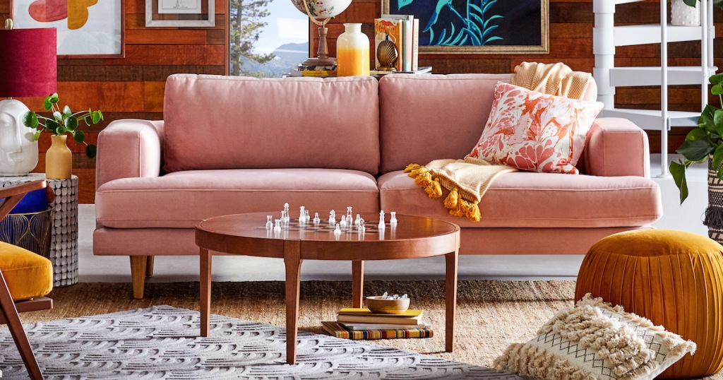 pink velvet sofa couch in eclectic styled living room with chess coffee table and other bold colored decor