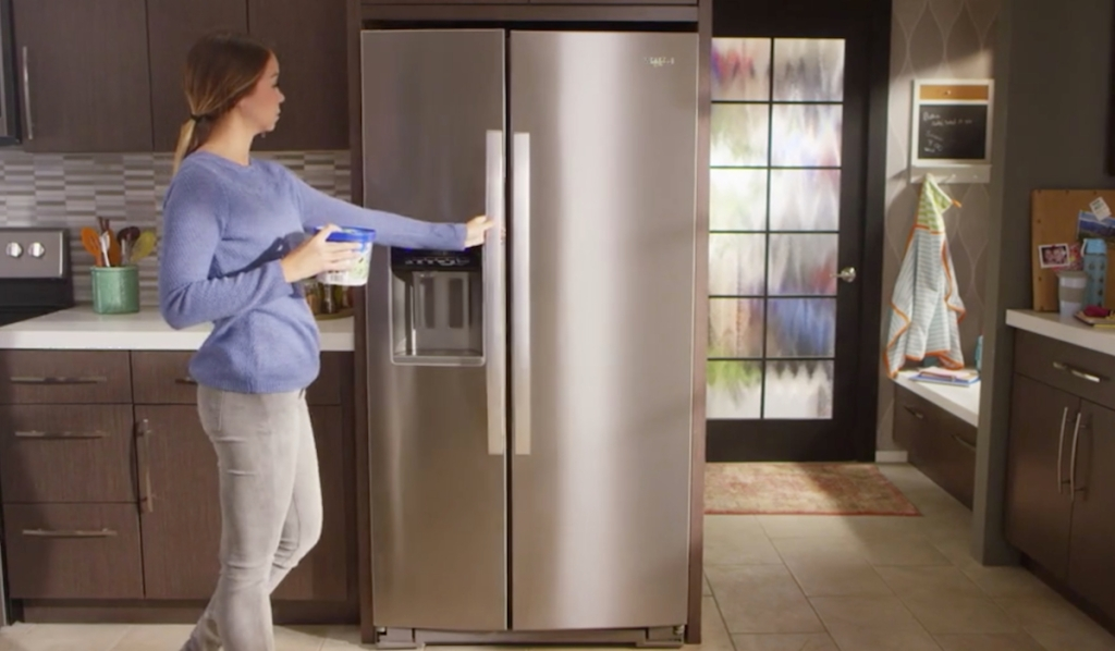 woman opening side by side stainless steel refrigerator door with brown wood cabinets surrounding it
