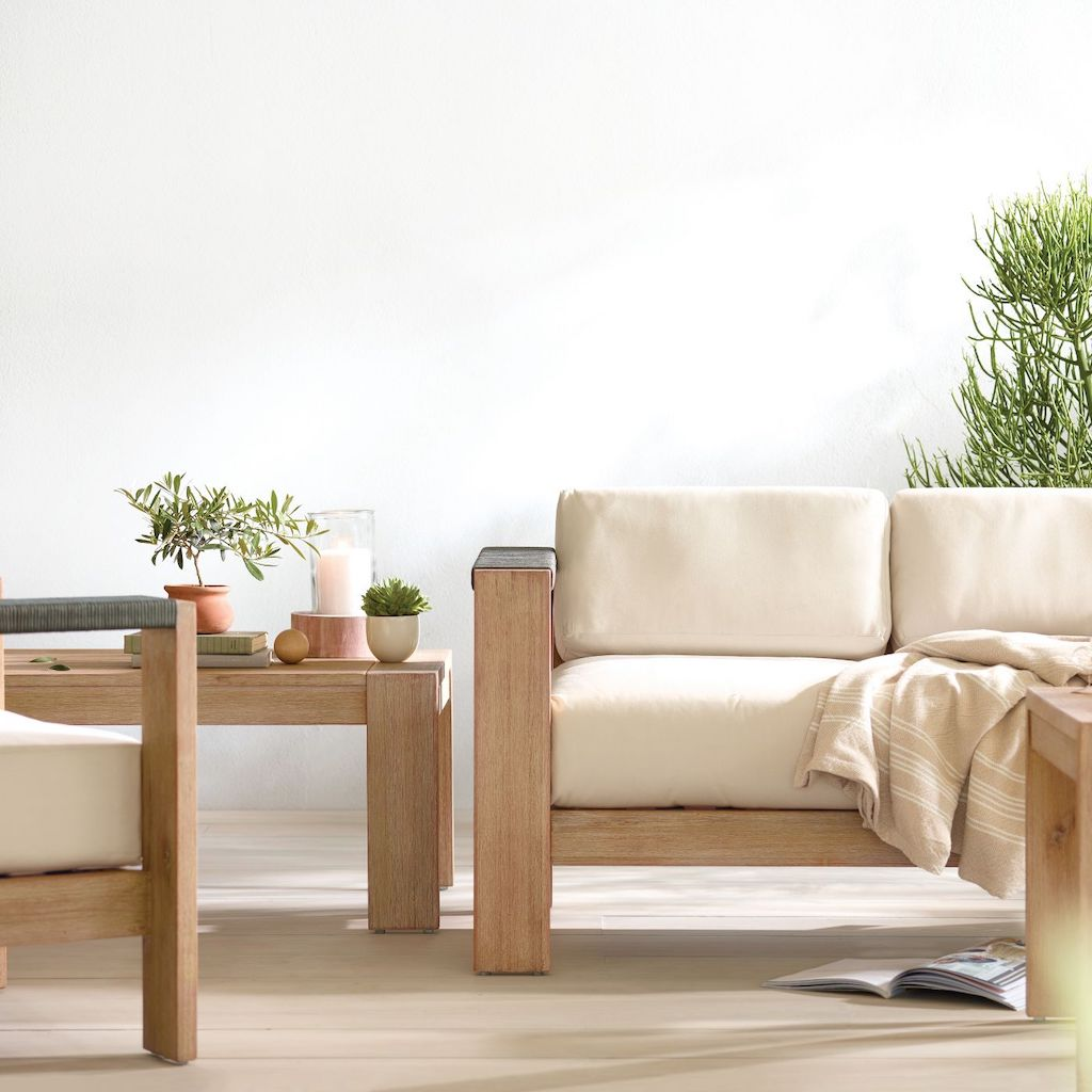 wood patio set with white cushions and plants