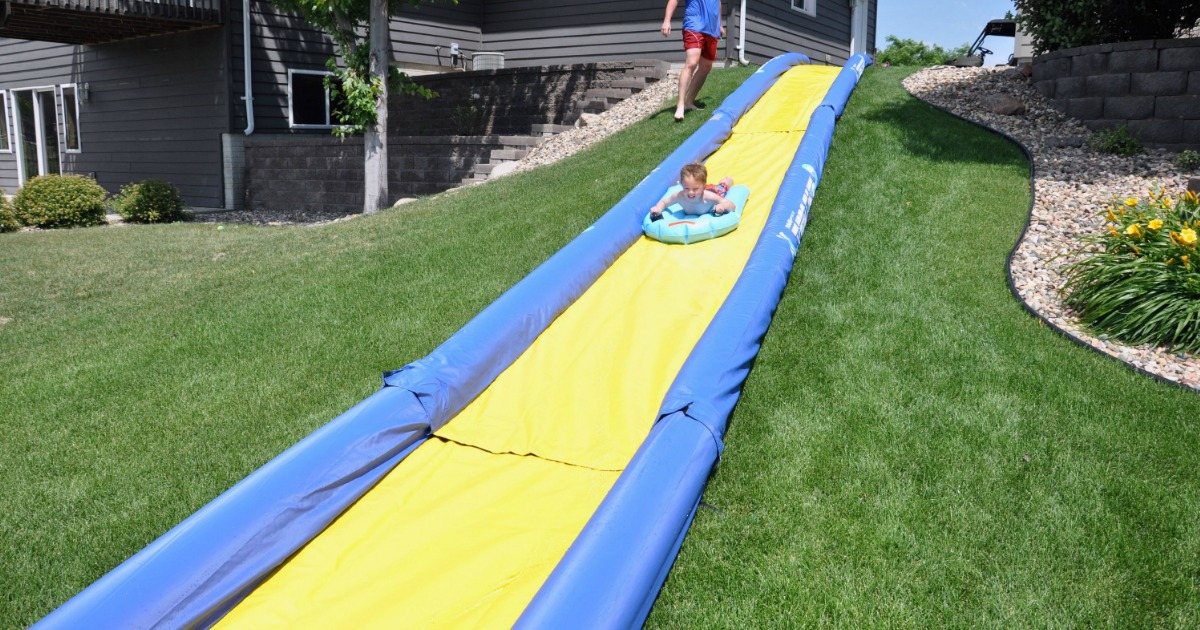 Boy on water sled sliding down super long yellow and blue water slide