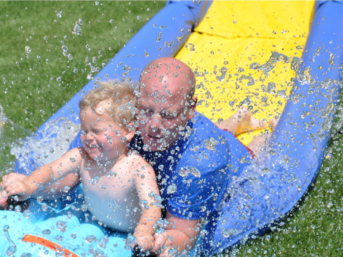 Dad and son sliding down a long PVC slide in grass