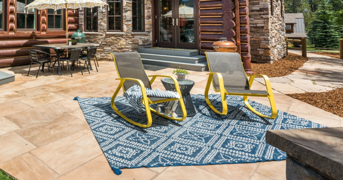 blue diamond rug on patio with two chairs on rug and house and table in background