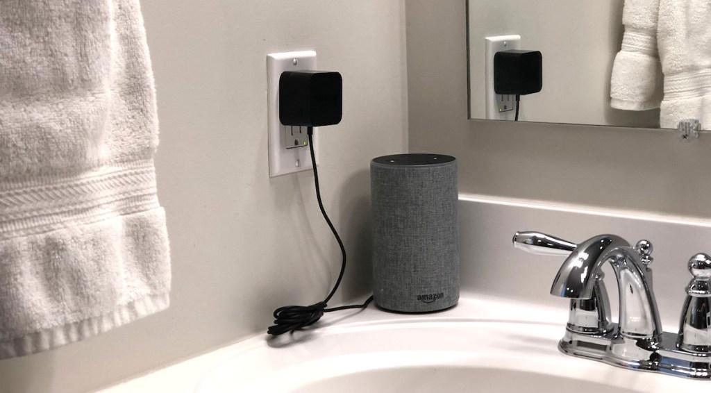 gray amazon alexa sitting on white counter in bathroom