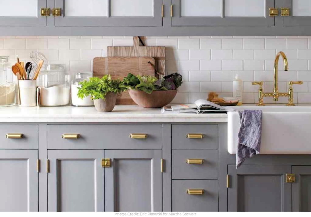 blue gray kitchen cabinets with brass hardware white sink and countertops