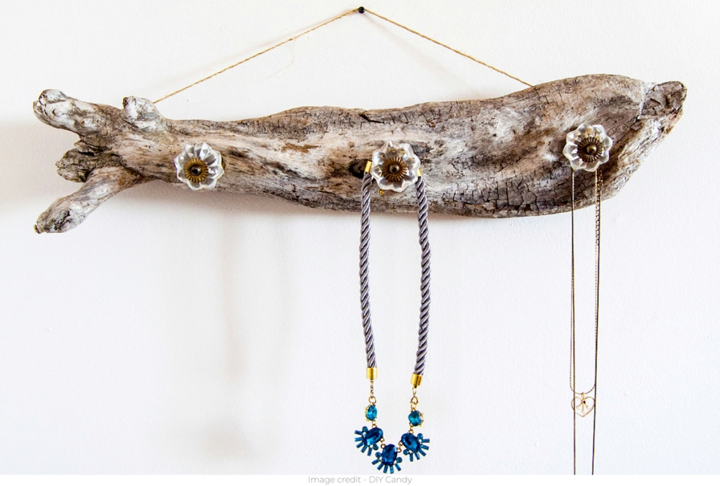 driftwood with crystal knobs and necklaces hanging on it