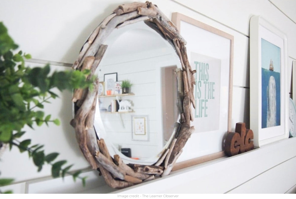round driftwood mirror sitting on white shelf with artwork