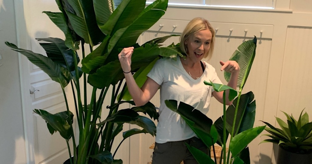 woman standing in the middle of two plants - one real and one fake