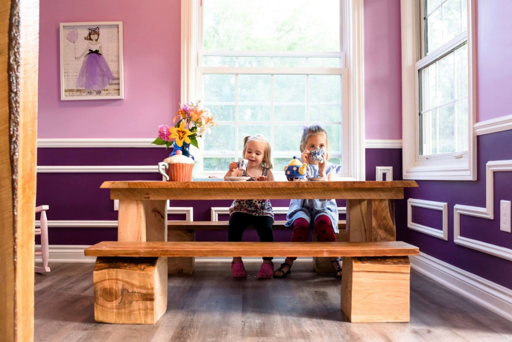 girls sitting at table having tea party