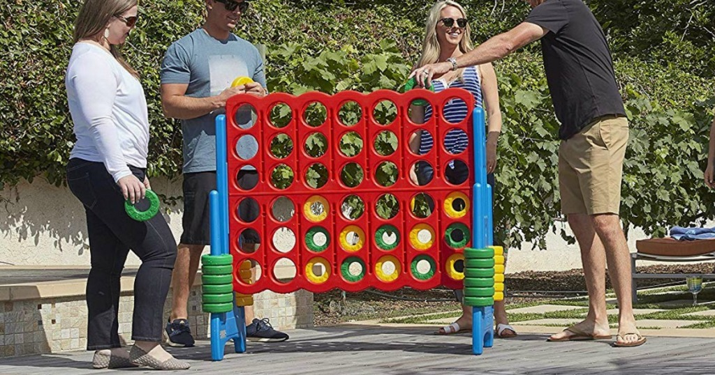 people playing large Connect 4 game in backyard