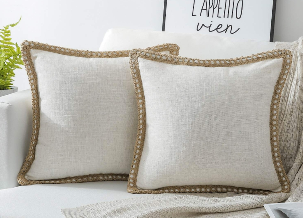 two white bordered pillows on white couch