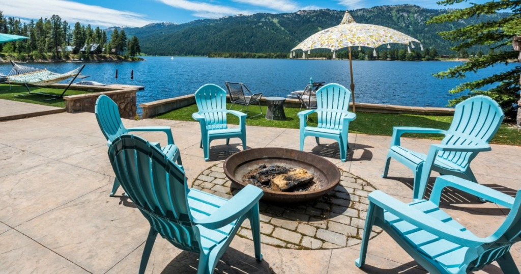 blue chairs sitting around a firepit on a patio with lake in the background