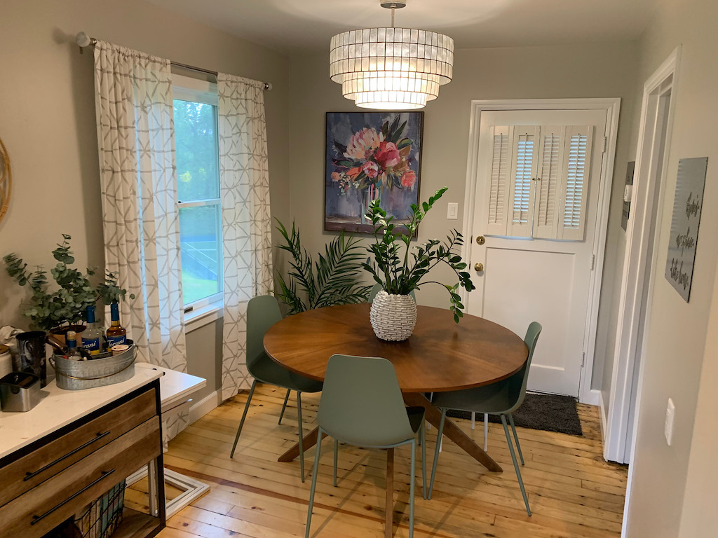 small dining room with a table, chairs, and plants