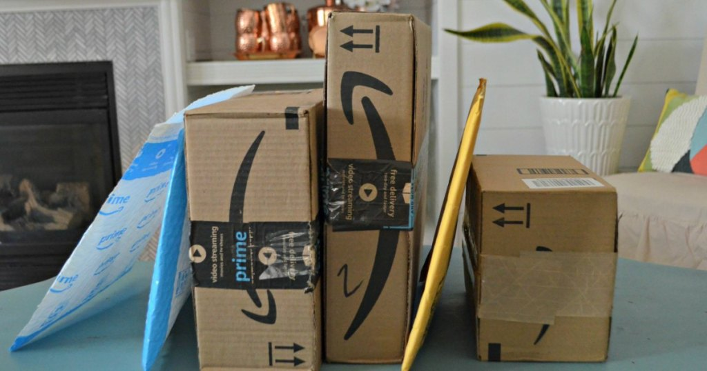 Amazon Prime boxes on dining table with plant and fireplace in the background