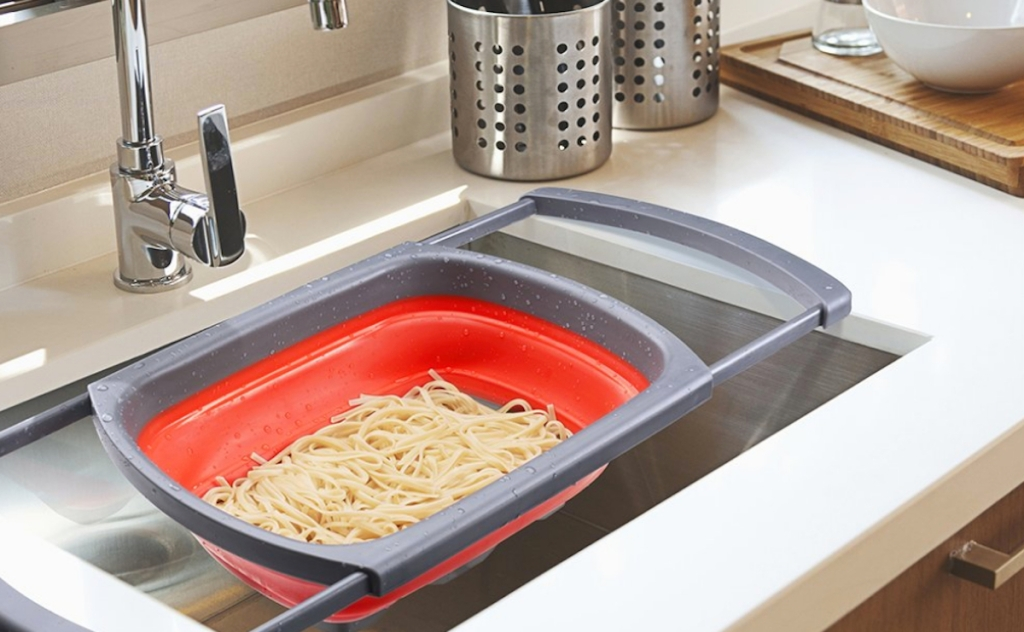 red colander in sink with pasta