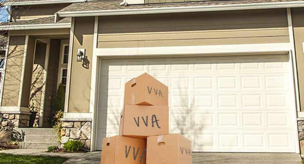 cardboard brown boxes on driveway in front of house