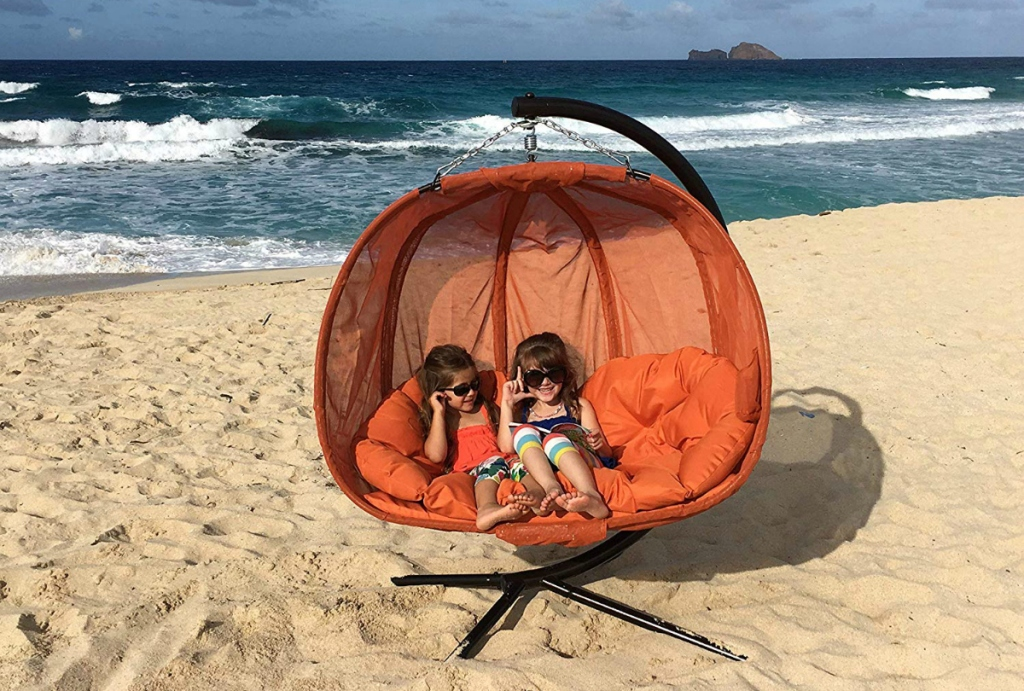 girls sitting in Flowerhouse Pumpkin Double Swing Chair with Stand on beach
