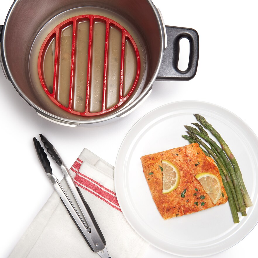 OXO pressure cooker rack in large pot next to plate with fish