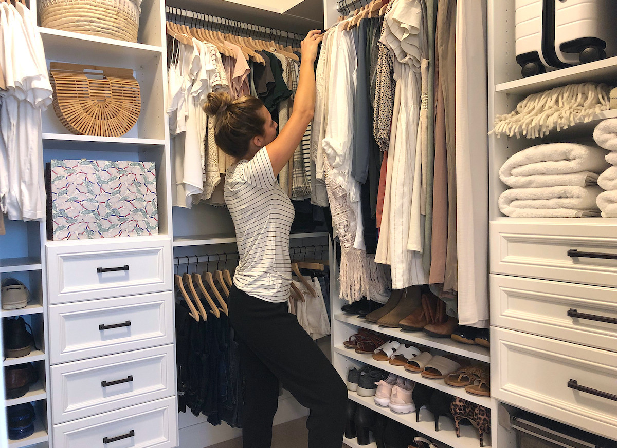 woman standing inside organized closet
