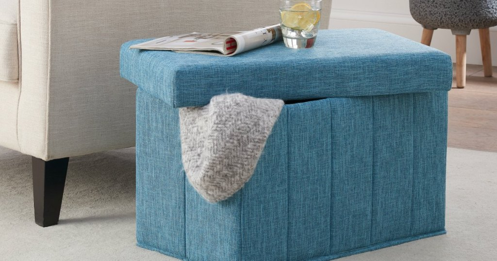 blue storage ottoman with blanket inside next to chair
