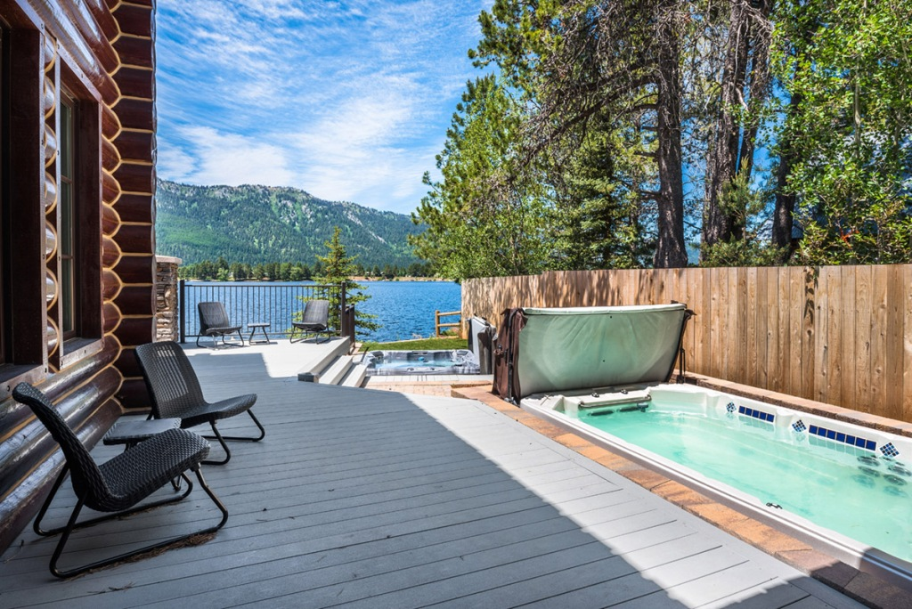 chairs sitting on deck by hot tub and lake