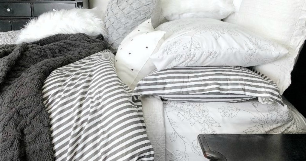 striped duvet set on bed with blankets and pillows