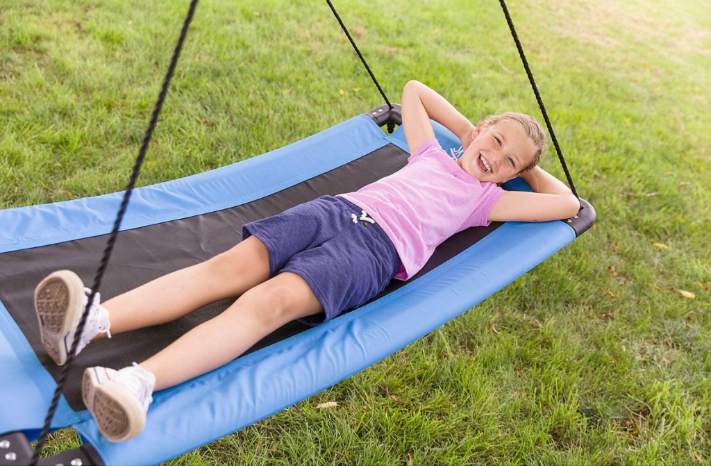 girl laying back on blue swing