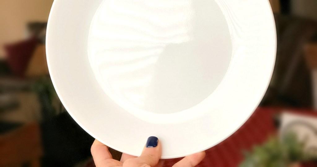 hand holding Corelle dinner plate