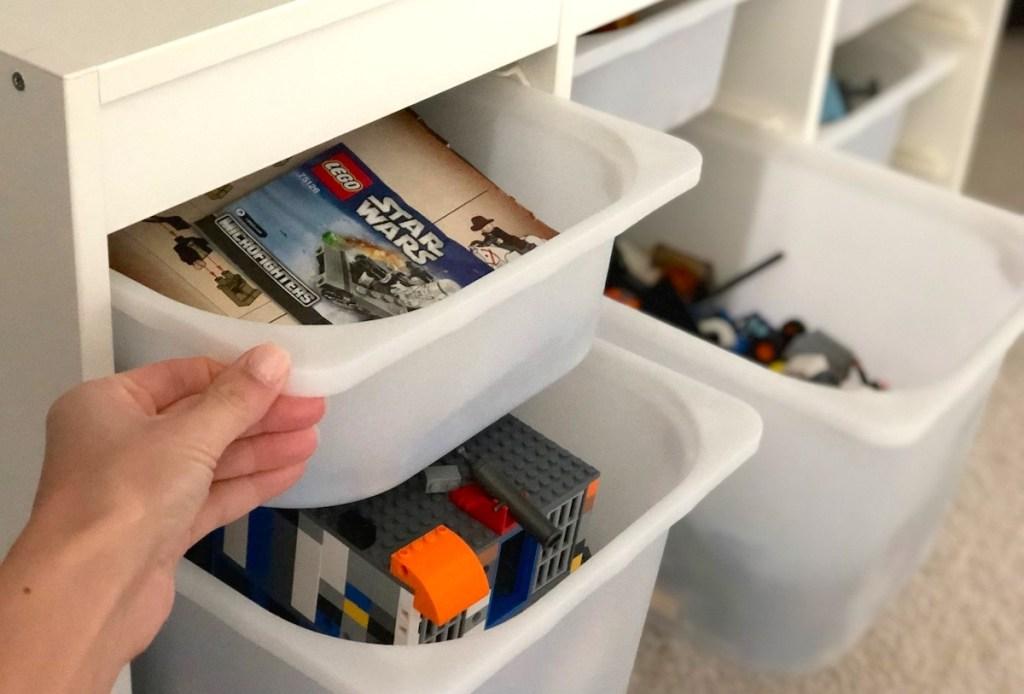 hand pulling white plastic bin with legos
