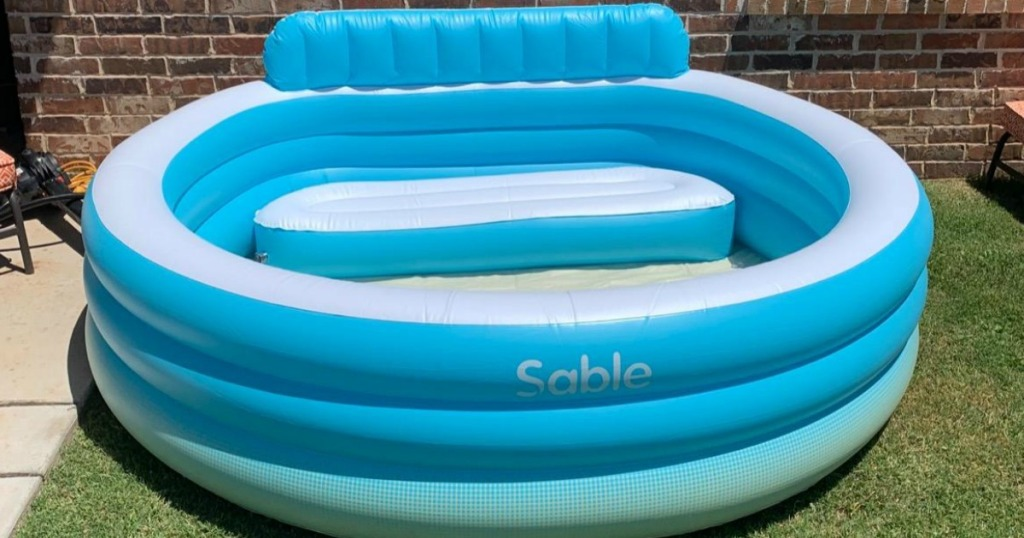 large inflatable pool with bench in backyard on grass