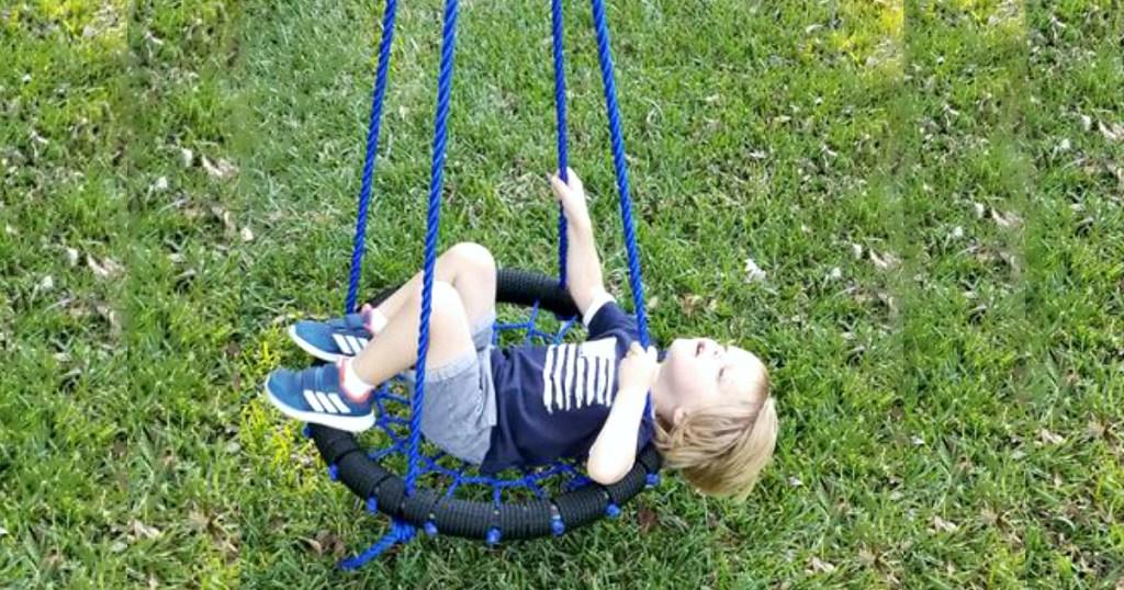 kid in blue black tree swing
