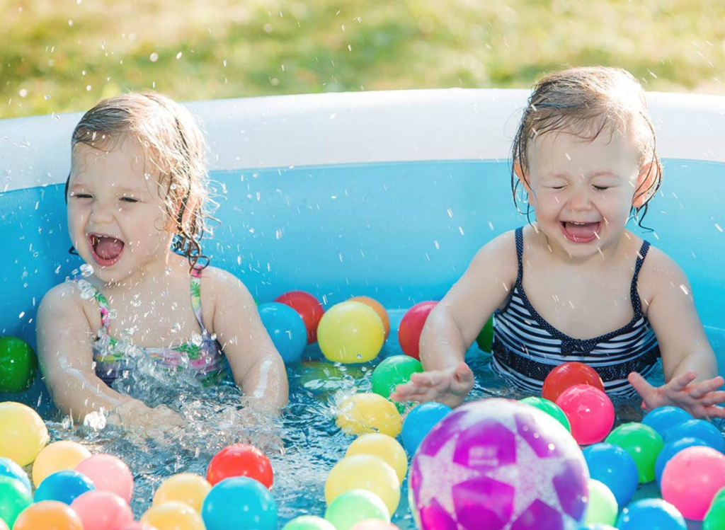 little girls having fun in inflatable pool with balls