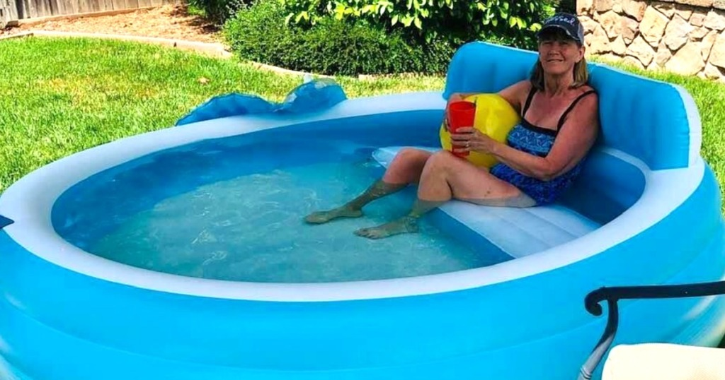 lady sitting in large inflatable pool with drink