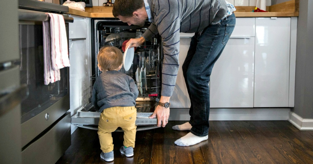 man and toddler loading dishwasher