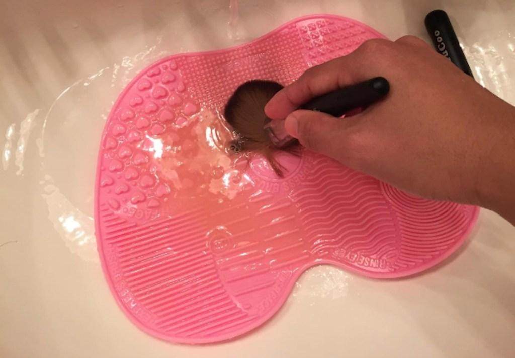 pink make up brush mat in sink