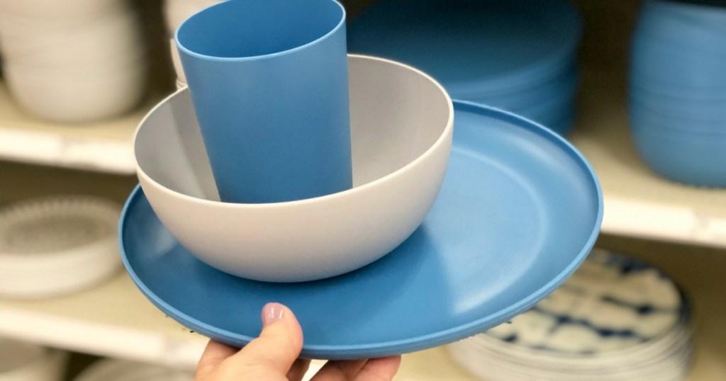 holding plastic dinnerware set at Target