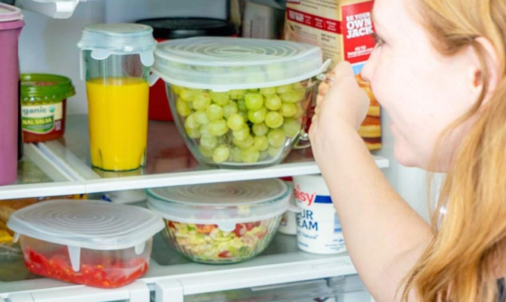 woman grabbing bowl of grapes from fridge