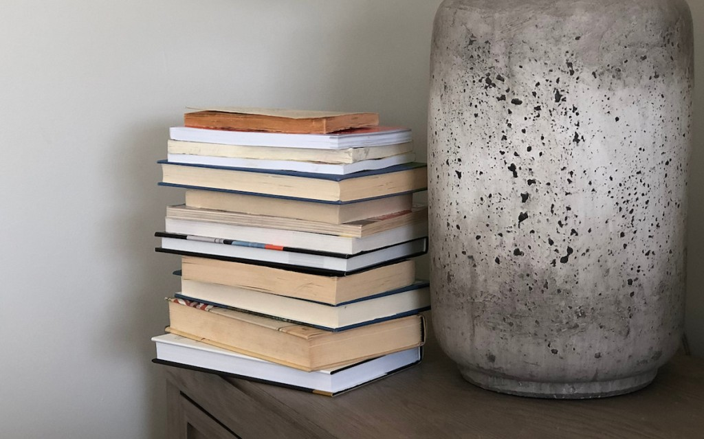 stack of books next to stone lamp