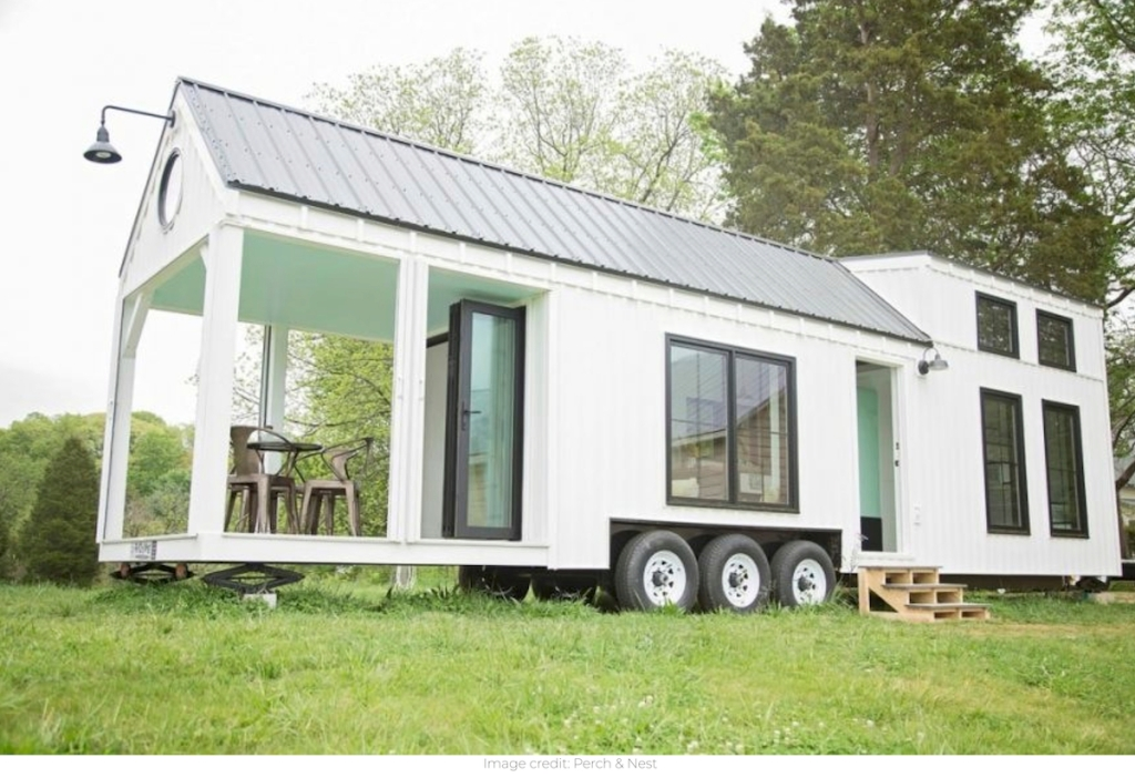 white tiny home parked in grass