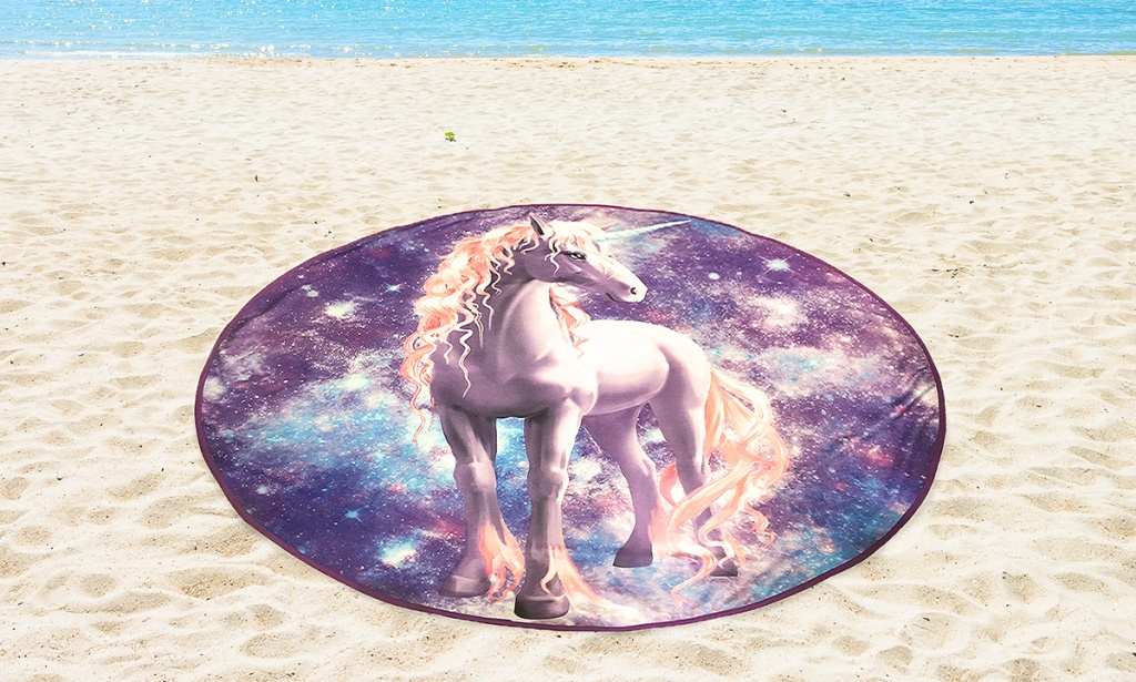 oversized circular unicorn towel on beach