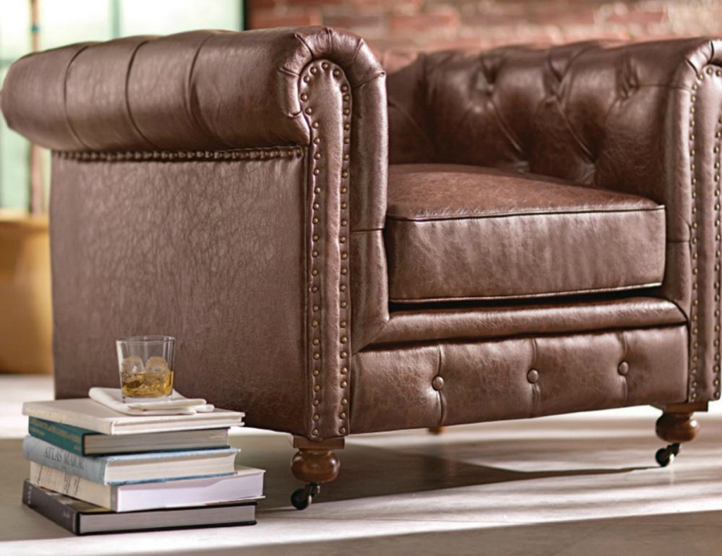 brown leather chair with books next to it